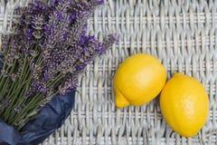 Lavendelbukett som slås in i papper med citroner på vide- bakgrund Arkivfoton
