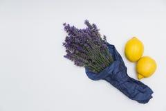 Lavendelbukett som slås in i papper med citroner på vit bakgrund Fotografering för Bildbyråer