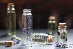Lavendelolja i en glasflaska Arkivfoto
