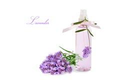 Lavendelproduct in nevelfles en geïsoleerde bloemen stock foto