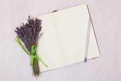 Lavendelschreibtisch auf Draufsichtspott des Hintergrundes oben Öffnen Sie Sketchbook Notizbuch Stockfotos