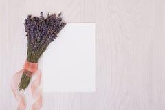 Lavendelschreibtisch mit Blumen auf Draufsichtspott des Hintergrundes oben Weißbuchpostkarte Stockfoto