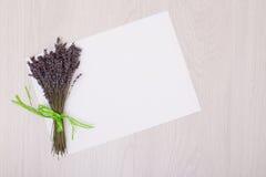 Lavendelschreibtisch mit Blumen auf Draufsichtspott des Hintergrundes oben Weißbuchpostkarte Lizenzfreies Stockfoto