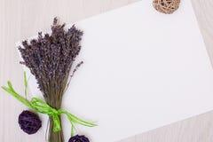 Lavendelschreibtisch mit Blumen auf Draufsichtspott des Hintergrundes oben Weißbuchpostkarte Lizenzfreie Stockbilder