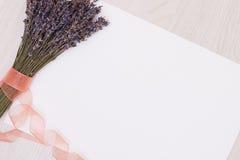 Lavendelschreibtisch mit Blumen auf Draufsichtspott des Hintergrundes oben Weißbuchpostkarte Lizenzfreie Stockfotografie