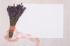 Lavendelschreibtisch mit Blumen auf Draufsichtspott des Hintergrundes oben Weißbuchpostkarte Lizenzfreies Stockbild
