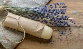 Lavendelseife mit einem Blumenstrauß des getrockneten Lavendels auf einem hölzernen Hintergrund Lizenzfreie Stockfotos