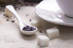 Lavendeltee im weißen keramischen Löffel mit Stücken Zucker, Textilhintergrund Stockfoto