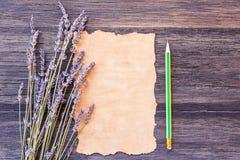 Lavender λουλούδι και παλαιό έγγραφο με το μολύβι στο παλαιό ξύλινο tabl Στοκ Εικόνες
