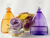 Lavender and arnica oil, rose petals. In a glass vase royalty free stock images