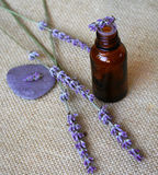 Lavender and bottle of essential oil on sackcloth Royalty Free Stock Photos