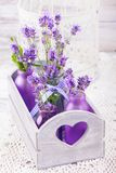 Lavender in bottles decor. Lavender in bottles, decor provance style, wooden box and birdcage on crochet tablecloth Stock Image