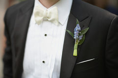 Lavender boutonniere. Flower on suit jacket of wedding groom royalty free stock images