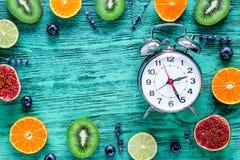 Lavender, clock, kiwi, citrus, fig on blue background top view mock up Stock Images