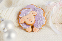 Lavender color gingerbread sheep on white knitted background Stock Photos