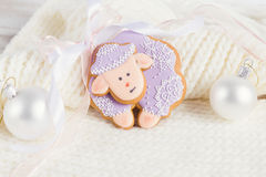 Lavender color gingerbread sheep on white knitted background. Lavender color gingerbread sheep with Christmas decoration on white knitted background stock images
