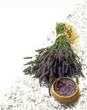 Lavender composition on white. Still life of a bunch of lavender flowers tied with a straw ribbon, with dried lavender seeds in a wooden bowl and more scattered Stock Photo