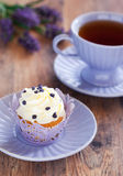 Lavender cupcake. Decorated with lavender sugar and cup of hot tea, selective focus Royalty Free Stock Photography