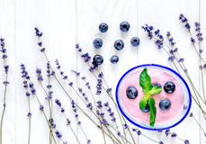 Lavender desk design with blueberry yoghurt white background top view mock up. Lavender desk design with blueberry yoghurt on white wooden background top view stock image