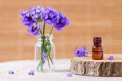 Lavender essential oil in a brown glass bottle and fresh lavender flowers on brown background Royalty Free Stock Images