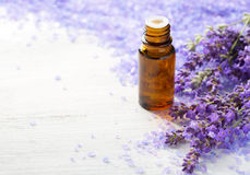 Lavender essential oil,   sprigs of lavender and  mineral bath salts on  the wooden table.  Selective focus.  Stock Photo