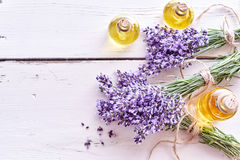 Lavender essential oils with fresh flowers. Lavender essential oils with bunches of fresh flowers tied with string on painted white wood boards with copy space royalty free stock image