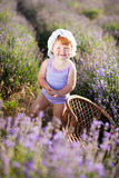Lavender fairy. Lovely red hair little girl near wattled armchair in a lavender field Royalty Free Stock Image