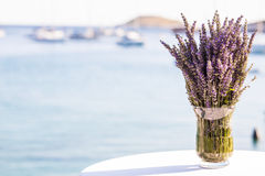Lavender Flowers. In a glass vase on a table by the ocean Royalty Free Stock Photos