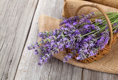 Lavender flowers in a basket with burlap. On the wooden background Stock Photos