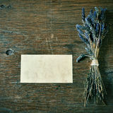 Lavender flowers and blank signboard on a rustic table. A bunch of lavender flowers and a blank signboard on a rustic wooden table stock image