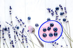 Lavender flowers with blueberry yoghurt mock up on white background top view. Lavender flowers with natural blueberry yoghurt mock up on white desk background stock photo