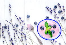 Lavender flowers with blueberry yoghurt mock up on white background top view. Lavender flowers with natural blueberry yoghurt mock up on white desk background stock photography