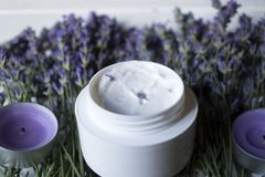 Lavender flowers, candles and cream on a white wooden background. stock image