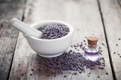 Lavender flowers in mortar and bottle of essential oil on wo Royalty Free Stock Image