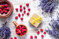 Lavender flowers with raspberry in cup on rustic background top Royalty Free Stock Images