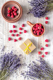 Lavender flowers with raspberry in cup on rustic background top view. Bunch of dry lavender flowers with raspberry in pottery cup and straw on rustic desk Royalty Free Stock Images