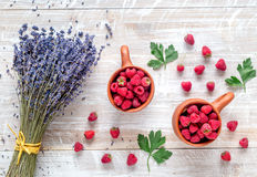 Lavender flowers with raspberry in cup on rustic background top view. Bunch of dry lavender flowers with raspberry in pottery cup and straw on rustic desk Royalty Free Stock Image