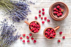 Lavender flowers with raspberry in cup on rustic background top view. Bunch of dry lavender flowers with raspberry in pottery cup and straw on rustic desk Royalty Free Stock Photos