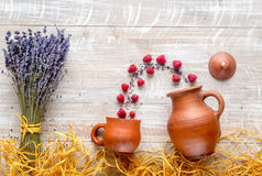 Lavender flowers with raspberry on rustic background top view mock up. Bunch of dry lavender flowers with raspberry in pots and straw on rustic desk background Royalty Free Stock Photography