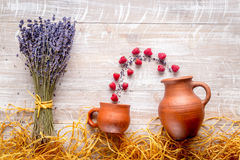 Lavender flowers with raspberry on rustic background top view mock up. Bunch of dry lavender flowers with raspberry in pots and straw on rustic desk background Stock Photos