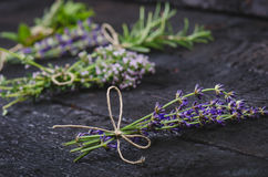 Lavender flowers, rosemary, mint, thyme, melissa with old scissors on a black wooden table. Burnt wood. Spa and cosmetic or cookin Stock Image