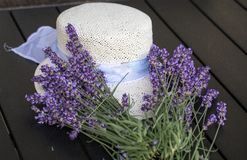 Lavender flowers and white hat on black table Stock Photos