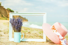 Lavender flowers, wooden frame and pink beach hat on the sand. In the background is a gentle azure sea, a coastline. Nobody. Mood is the concept of leisure Royalty Free Stock Images