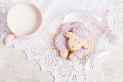 Lavender gingerbread sheep with cup of milk on lace tablecloth. Stock Photo