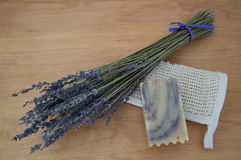 Lavender Goats Milk Soap on Folded Ramie Washcloth. Close up of lavender goats milk soap with purple swirls on a folded ramie washcloth with a bouquet of dried royalty free stock photos