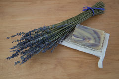 Lavender Goats Milk Soap with Lavender Sprigs. Close up of lavender goats milk soap with purple swirls on a folded ramie washcloth with a bouquet of dried stock photos