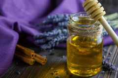 Lavender and herbal honey in glass jar with honey spoon on dark wooden background stock photos