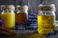 Lavender and herbal honey in glass jars and lavender flowers on dark wooden background royalty free stock photo