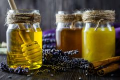 Lavender and herbal honey in glass jars with honey spoon on dark wooden background stock photo