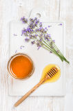 Lavender honey in glass jar with flowers on white background Royalty Free Stock Photography